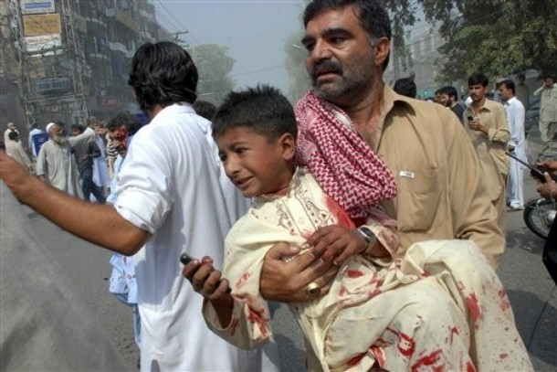 Pakistani volunteer takes away an injured boy from the site of a bomb explosion in a commercial district in Peshawar, Pakistan on Saturday, Sept. 26, 2009